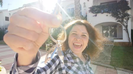 oneperson : Happy young Woman moving into new home. Showing keys of new property Stock Footage