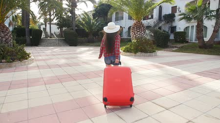 voyager : Toung woman with a red suitcase running on a resort