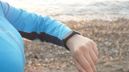 fitness tracker : Smart watch woman using smartwatch touching button outdoors Stock Footage