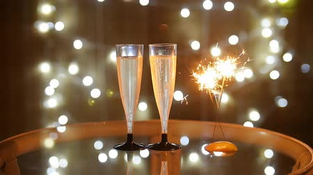 champagne bottles : New Year Celebration with two champagne glasses and sparkler Stock Footage