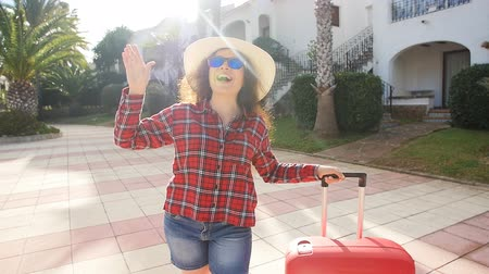 тянуть : Happy young woman with red suitcase arriving to the resort or apartment Стоковые видеозаписи