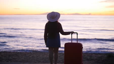 vocação : Young woman in a hat with a suitcase on the beach Vídeos
