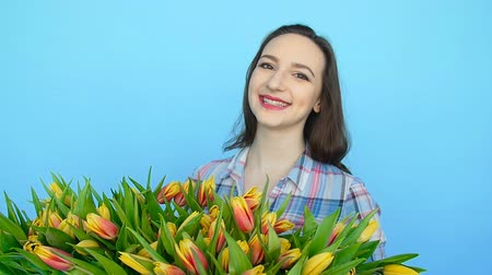 florista : Young woman holding a box with tulips on a blue background Vídeos