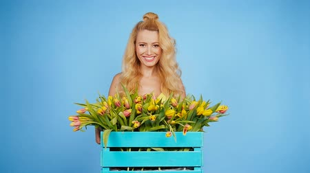 floriculture : Young blonde woman with tulips on blue background