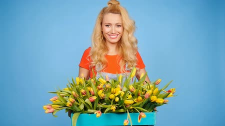 садовник : Young female florist with big box of yellow tulips Стоковые видеозаписи