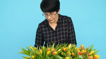 flower shops : A middle-aged woman with flowers. The concept of floristry Stock Footage