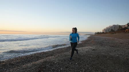footing : Mujer que corre cerca del mar al atardecer Archivo de Video