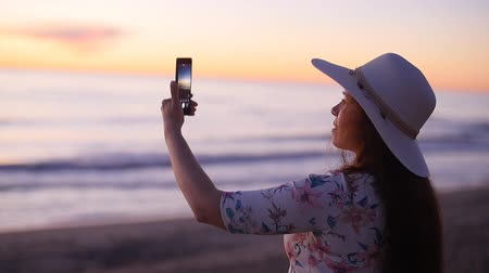 fotoğrafçı : Young woman taking photos with her smartphone on beach