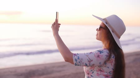 elfog : Young woman taking photos with her smartphone on beach