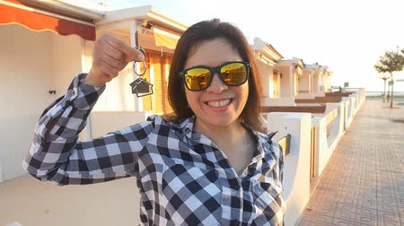 инвестирование : Happy smiling woman holding house keys of her new house