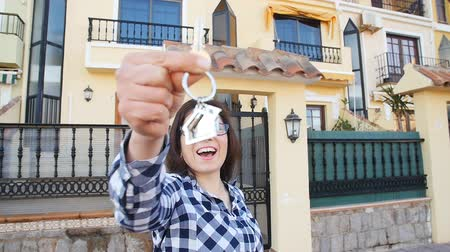 investimento : Happy smiling woman holding house keys of her new house