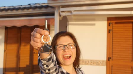 pożyczka : Happy young woman with New House Keys outdoors