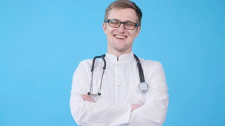 kifejező pozitivitás : Smiling young doctor in white uniform looking at camera