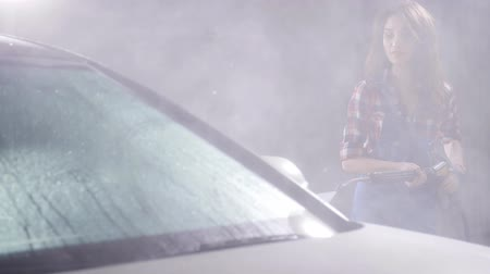 grime : Young woman washes car with high pressure washing machine