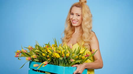 florista : Cheerful young woman florist holding box of tulips