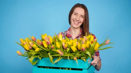 virágárus : Cheerful young woman florist holding box of tulips