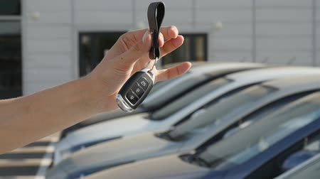 давать : Hand with a key on the background of a row of new cars