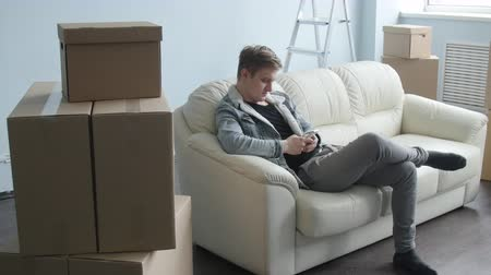 recipiente : Young man moved to a new apartment. Sits on the couch with a smartphone