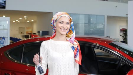 loans : A young Muslim woman with keys from a new car Stock Footage