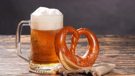 Октоберфест : A glass of beer and pretzel on a wooden table