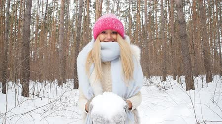 snowy background : Young woman throws snow up with a nice smile in the winter forest