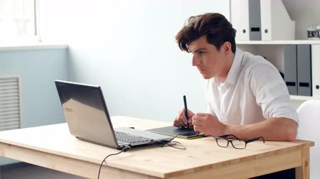 digitized : Casual male designer using graphics tablet in a bright office
