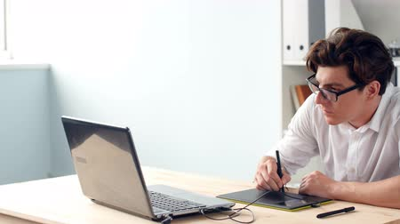 focus on foreground : Casual male designer using graphics tablet in a bright office