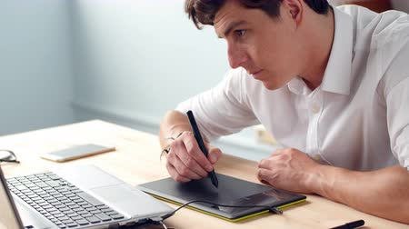using stylus : Casual male designer using graphics tablet in a bright office