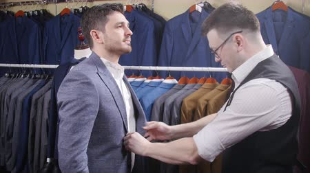 casual wear businessman : Man helps another try on a suit in a clothing store Stock Footage