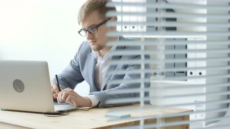 jurist : Young man designer in glasses works on a graphic tablet Stock Footage