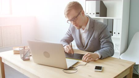 solicitor : Young man designer in glasses works on a graphic tablet Stock Footage