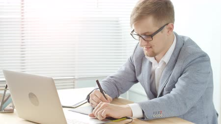 wąsy : Young man designer in glasses works on a graphic tablet Wideo