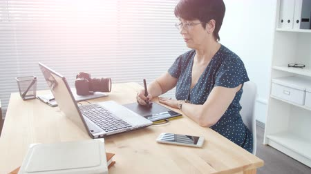 редактировать : Graphic designer aged woman using digital graphic tablet while working at modern office