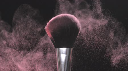 süspansiyon : Make-up brushes with pink powder on a black background in slow motion