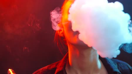 inhaling : Night life concept. Young woman smokes electronic cigarette in color light