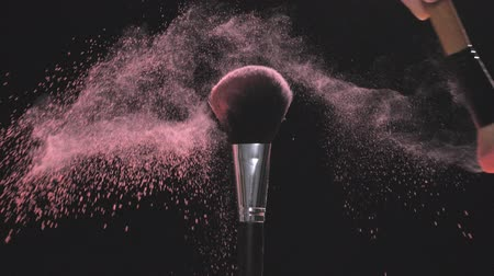 beauty products : Two Make-up brushes with pink powder on a black background Stock Footage