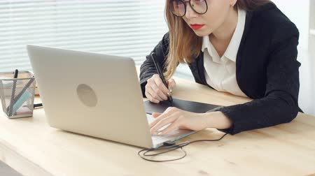concentrando : Young woman graphic designer working on laptop using tablet at modern office Vídeos