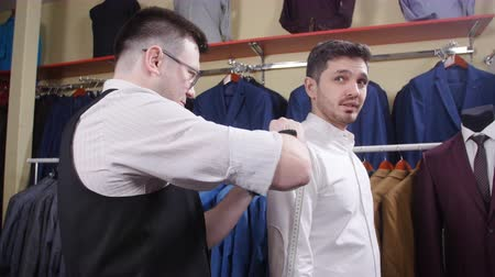 oszlopsor : Man suit concept. Seller helps the buyer choose a suit in the clothing store