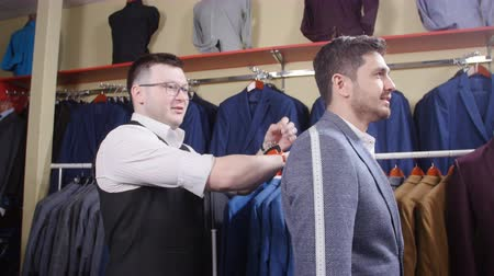 přezka : Man suit concept. Seller helps the buyer choose a suit in the clothing store