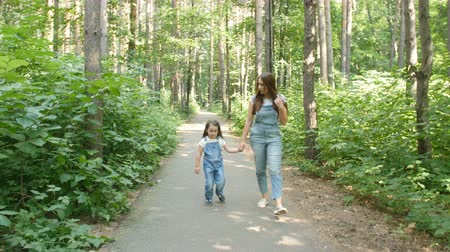 stroll : Family concept. Young mother and child daughter holding hands and walk Stock Footage