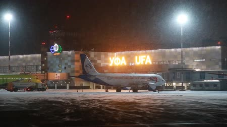 zástěra : UFA, RUSSIA - APRIL 1, 2018: Ufa International Airport. View to the night winter airfield and airplanes of Aeroflot Airlines. Dostupné videozáznamy