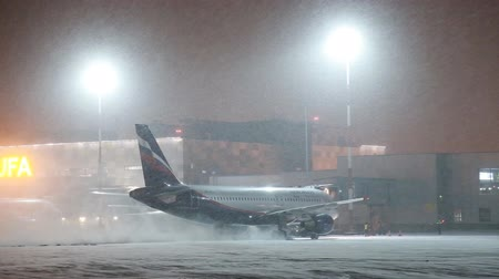 airfield : UFA, RUSSIA - APRIL 1, 2018: Ufa International Airport. View to the night winter airfield and airplanes of Aeroflot Airlines. Stock Footage