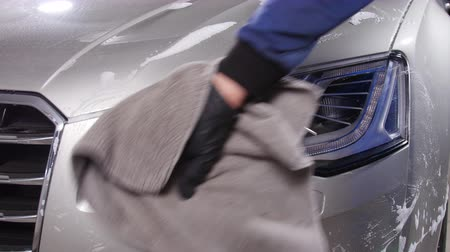 sabão : Car detailing concept. Man holds the microfiber in hand and polishes the car