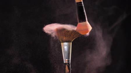 beauty products : Cosmetic and beauty concept. Cosmetic brush with pastel pink cosmetic powder on black background