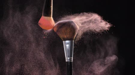 paint splash : Two Make-up brush with pink powder on black background