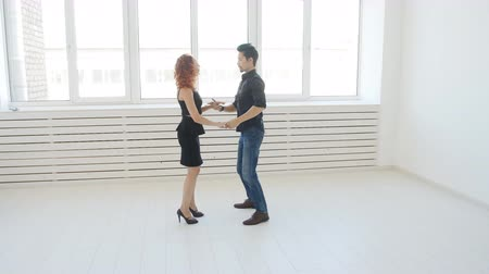 atitude : Beauty young couple dancing social dance in a white room. Kizomba or bachata or semba or taraxia