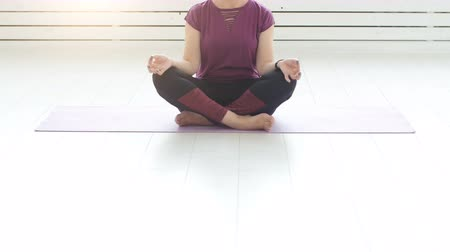 clasped : Middle-aged woman doing yoga in white interior at home