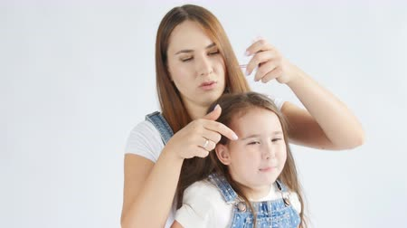 contato com os olhos : Happy Mother is brushing her lovely daughters hair on a white interior Vídeos