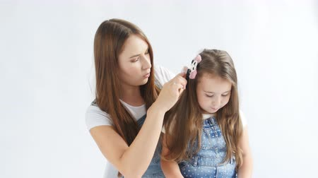 kartáč na vlasy : Happy Mother is brushing her lovely daughters hair on a white interior Dostupné videozáznamy