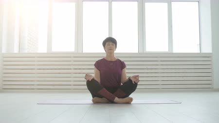 meditando : Middle aged yogi attractive woman practicing yoga indoors